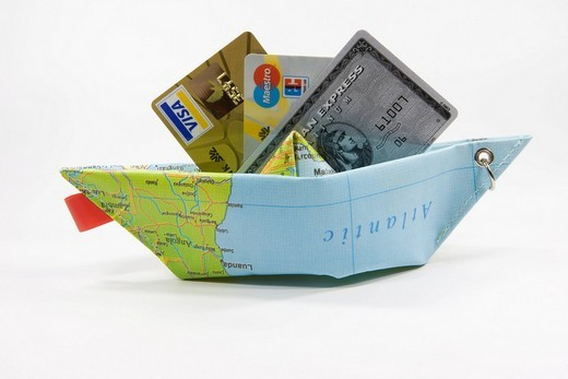 Credit cards and a paper ship made from a map: symbol for payment methods while travelling : Stock Photo