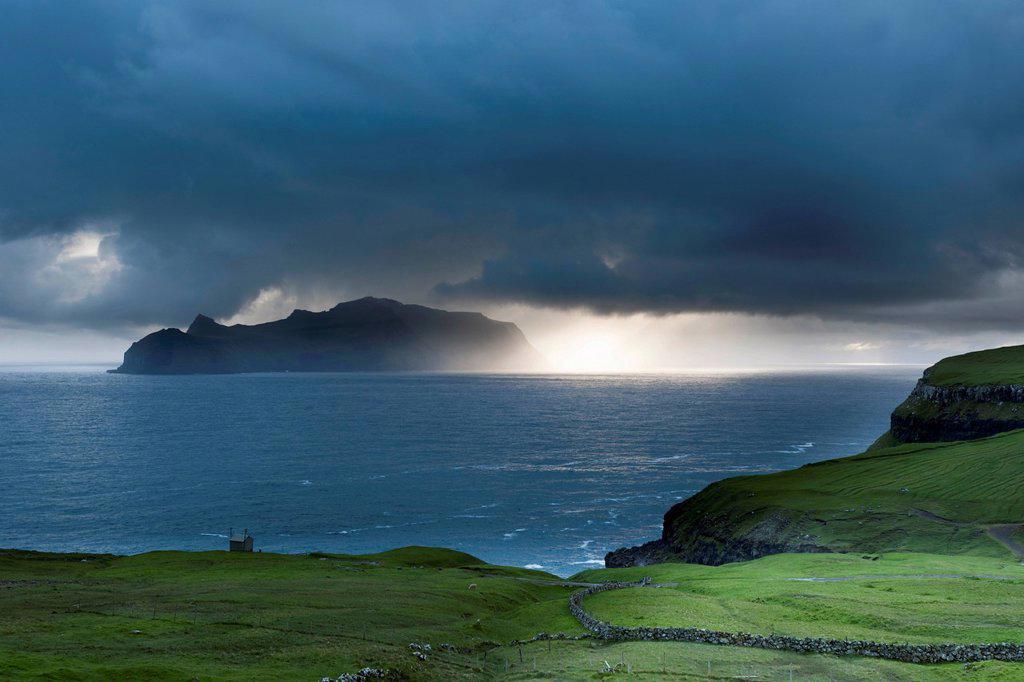Last evening sun rays over the island of Mykines in the North Atlantic, Faroe Islands, North Sea, Northern Europe, Europe : Stock Photo