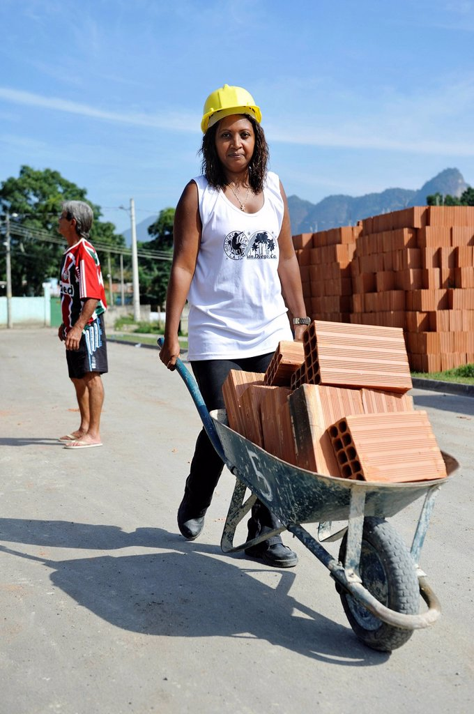 Stock Photo: 1848-742516 Woman from the slums, favelas, transporting bricks in a wheelbarrow on a building site of the Esperanca housing co_operative, each family helping out on the project and committing to small monthly payments, will get their own house, Jacerepagua neighbourh. Woman from the slums, favelas, transporting bricks in a wheelbarrow on a building site of the Esperanca housing co_operative, each family helping out on the project and committing to small monthly payments, will get their own house, Jacerepagu