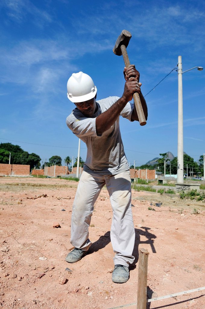 Stock Photo: 1848-742517 Man with a sledge hammer hitting a peg in the ground, people from the slums, favelas, working together on a building site of the Esperanca housing co_operative, each family helping out on the project and committing to small monthly payments, will get thei. Man with a sledge hammer hitting a peg in the ground, people from the slums, favelas, working together on a building site of the Esperanca housing co_operative, each family helping out on the project and committing to small monthly payments, w