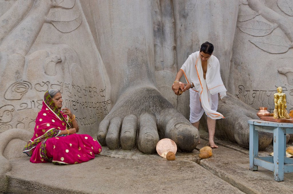 Stock Photo: 1848-744133 Priest is pouring water on the feet of the gigantic statue of Gomateshwara in Sravanabelagola, pilgrim meditating, Sravanabelagola, India, Asia