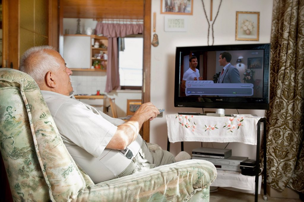 Elderly man sitting in front of a TV operating a remote control : Stock Photo