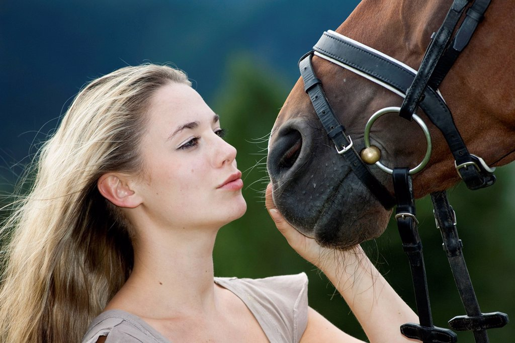 Young woman cuddling with an Oldenburger horse, bay, North Tyrol, Austria, Europe : Stock Photo