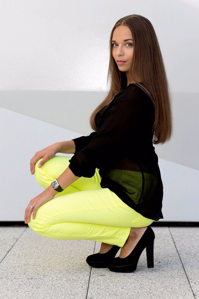 Young woman with a black top, bright yellow trousers and black high heels : Stock Photo