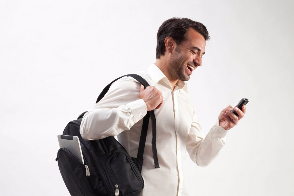 Stock Photo: 1848-745505 Smiling man wearing a backpack, from which an iPad is sticking out, talking on a mobile phone