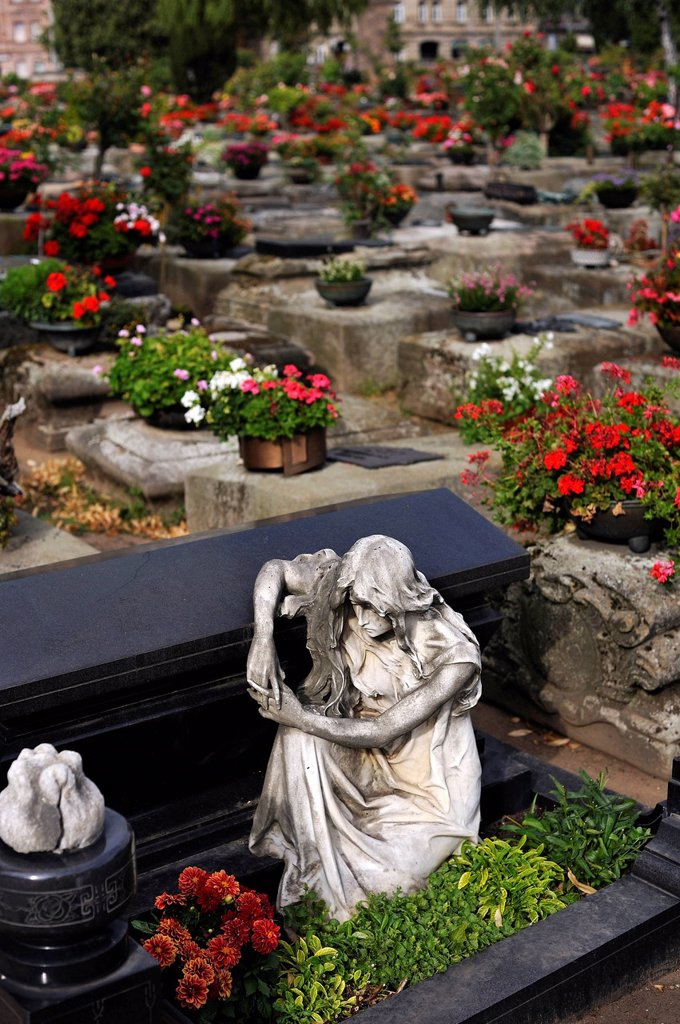 Sculpture of a mourner at a sarcophagus in front of other graves with flowers, St. John´s Cemetery, Nuremberg, Middle Franconia, Bavaria, Germany, Europe : Stock Photo