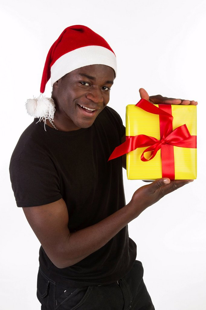Stock Photo: 1848-747588 Young black man wearing a Santa hat and holding a present