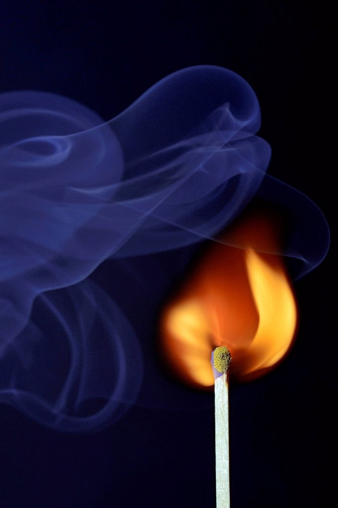 Matchstick being ignited, with blue smoke : Stock Photo
