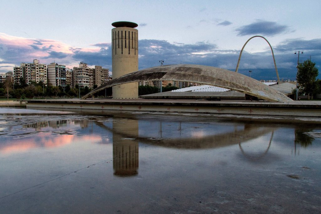 Expo site, Rachid Karami International Fair, Tripoli, Lebanon. The Brazilian architect Oscar Niemeyer was planning the area in the early 1960s. Observation tower, outdoor stage and bow in front of the city skyline. : Stock Photo