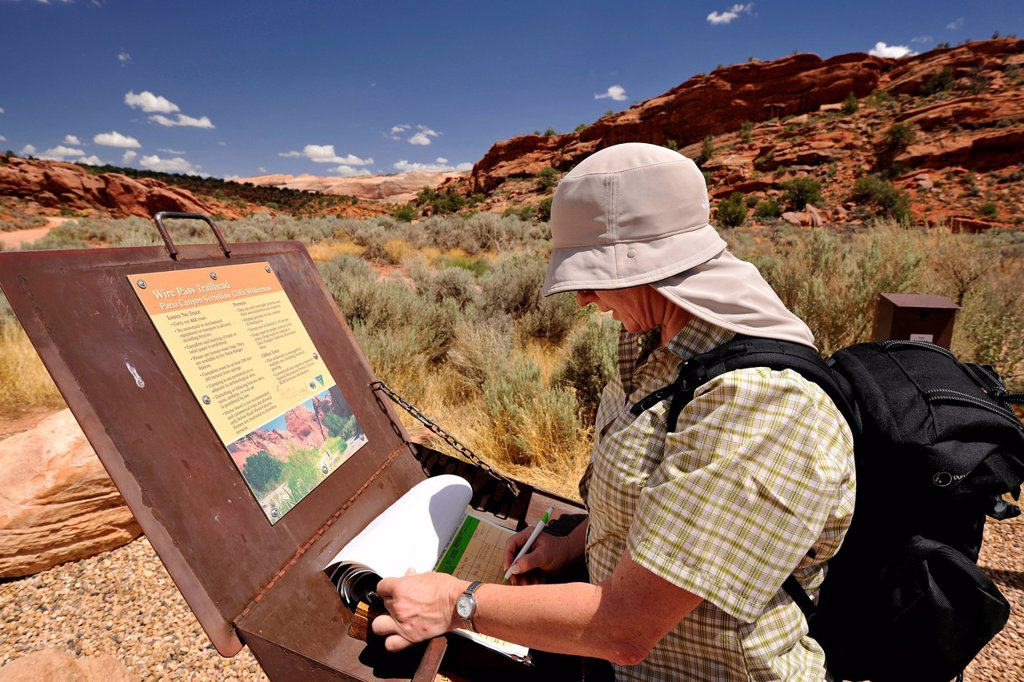 Stock Photo: 1848-750896 Tourist with a sun shield signing the registration box at Trailhead Wirepass, starting point to The Wave Navajo sandstone rocks, North Coyote Buttes, CBN, Pahreah Paria Canyon, Vermilion Cliffs National Monument, Arizona, Utah, Südwesten, Vereinigte Staat. Tourist with a sun shield signing the registration box at Trailhead Wirepass, starting point to The Wave Navajo sandstone rocks, North Coyote Buttes, CBN, Pahreah Paria Canyon, Vermilion Cliffs National Monument, Arizona, Utah, Südwesten, Vere