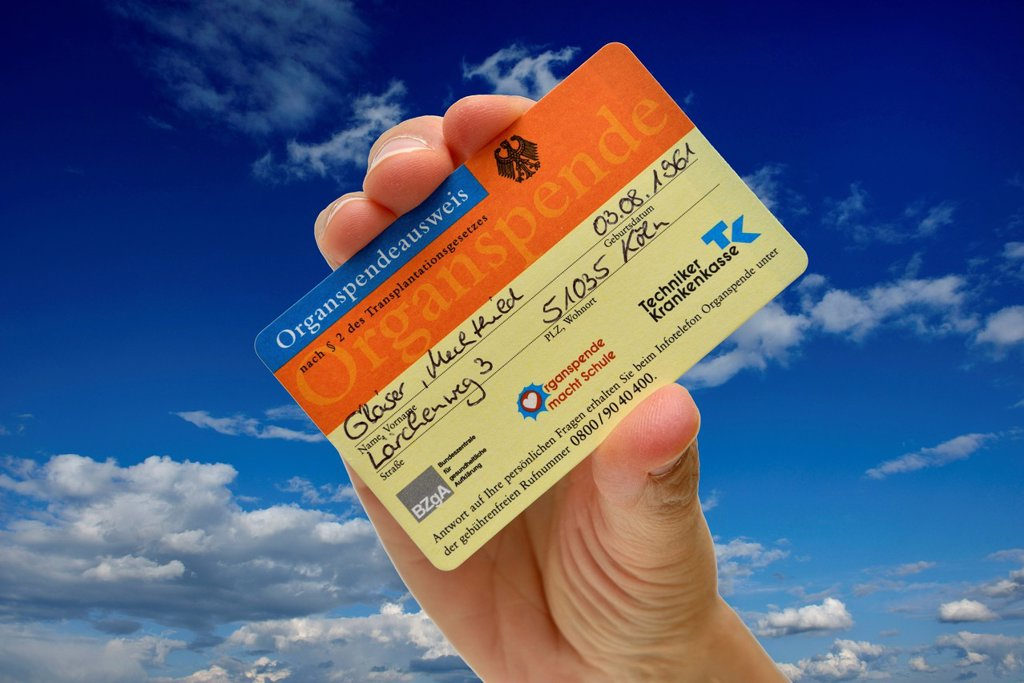 Stock Photo: 1848-751075 Hand holding an organ donor card, fake name, against a blue sky with some clouds, symbolic image for bearer of hope, organ donation