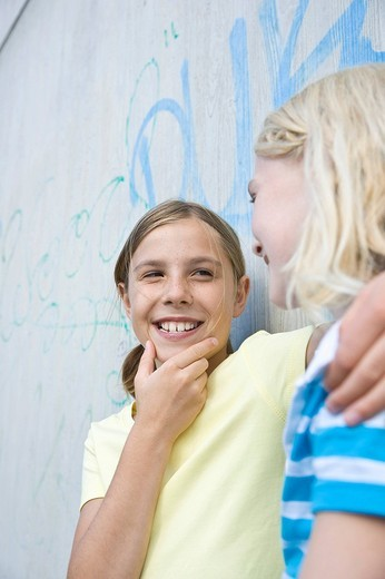 Two girls leaning against a wall, talking : Stock Photo