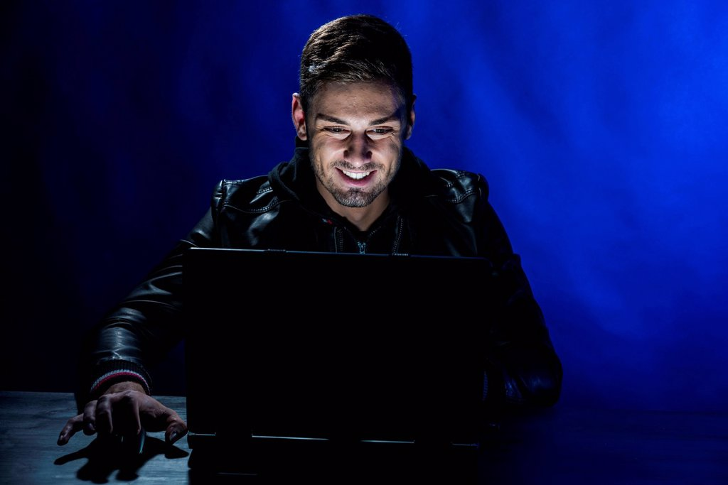 Young man sitting in the dark in front of a laptop, with a joyful expression : Stock Photo