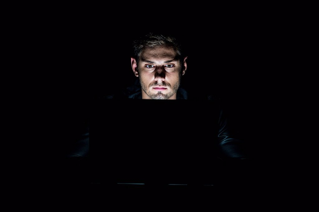 Young man sitting in front of a laptop in the dark, illuminated only by the monitor : Stock Photo