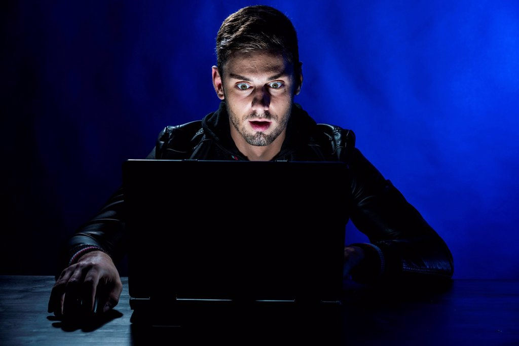 Stock Photo: 1848-753563 Young man sitting in the dark in front of a laptop, with a shocked facial expression