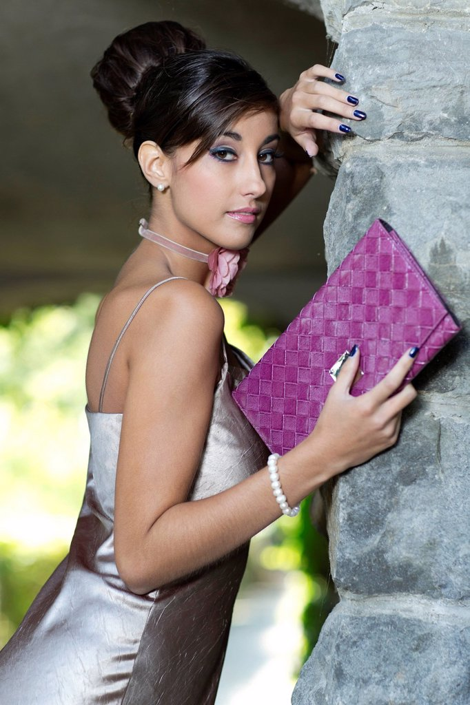 Stock Photo: 1848-755600 Young woman with an updo hairstyle, silvery evening gown and clutch, posing in front of a stone wall