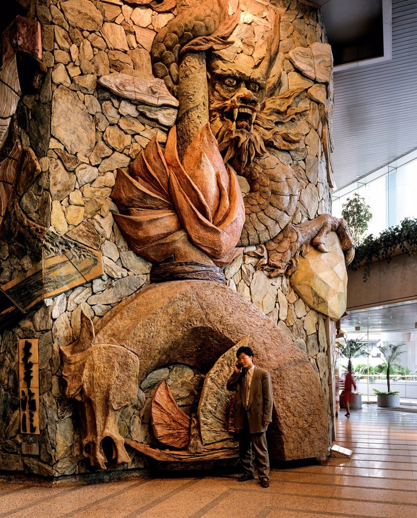 Lobby of the Lippo Centre, artwork made of stone with a man using a mobile phone standing in front, detail, glass facade, Central District, Victoria Island : Stock Photo