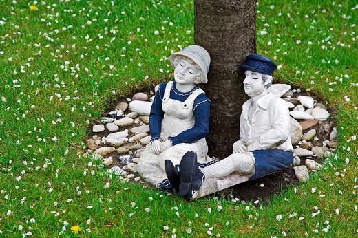 Woman and man, pair of figurines made of plaster, are leaning against a tree trunk : Stock Photo