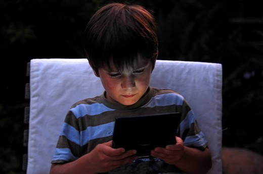 Little boy playing with his DS game, Dual Screen Game : Stock Photo