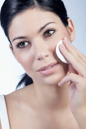 Young woman using a cotton pad for cleansing, beauty : Stock Photo