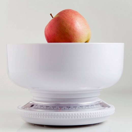 Apple in a kitchen scale : Stock Photo