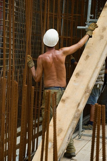 Construction worker with bare torso connecting steel rod mats, preparing for the pouring of cement, Germany, Europe : Stock Photo