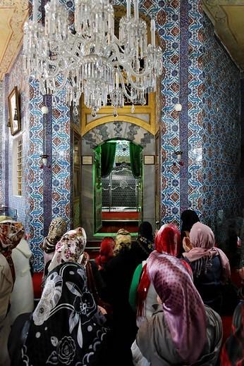 Muslim women pray in front of the tomb of Mohammed´s standard_bearer Eyuep Ensari, mausoleum, Tuerbesi, Eyuep village, Golden Horn, Istanbul, Turkey : Stock Photo