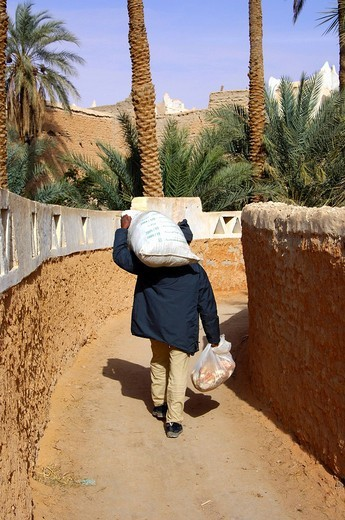 Stock Photo: 1848-79896 Man returning from the market with heavy bags, Old town of Ghadames Libya