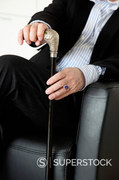 Stock Photo: 1848-801085 Senior sitting in a chair holding a walking cane