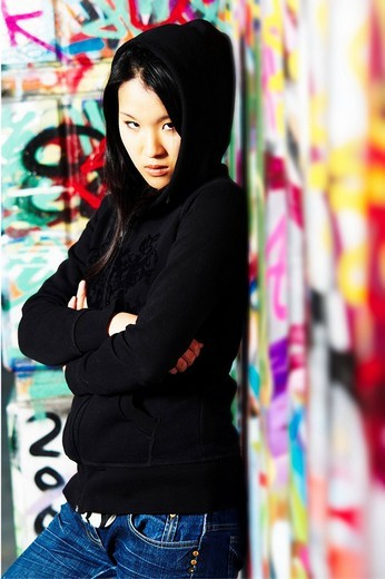 Young Asian girl in rapper pose in front of a wall with graffiti : Stock Photo