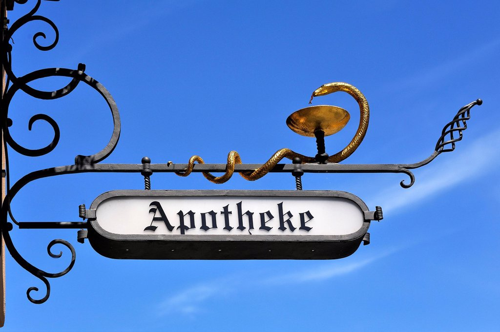Stock Photo: 1848-812083 Hanging sign of St. George Apotheke pharmacy against a blue sky