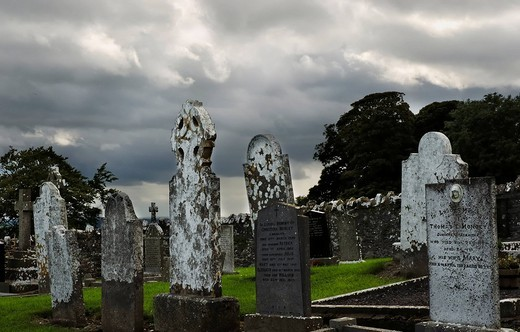 Shower clouds flying by weathered tombstones at old cemetery, Slane Co Meath Ireland : Stock Photo
