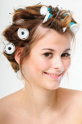 Pretty young brunette woman with curlers in her hair : Stock Photo