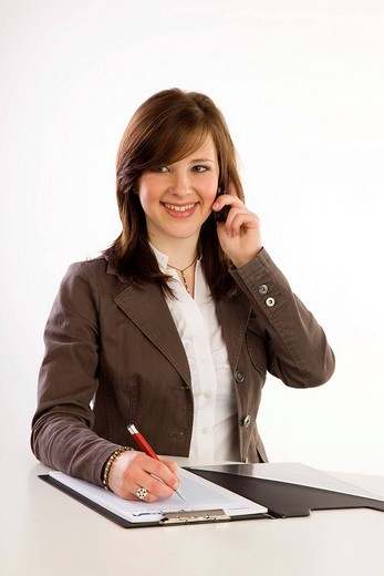 Stock Photo: 1848-82988 Young woman with cell phone and notepad smiling