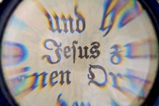 The Word Jesus in an old Bible, seen through a magnifying glass : Stock Photo