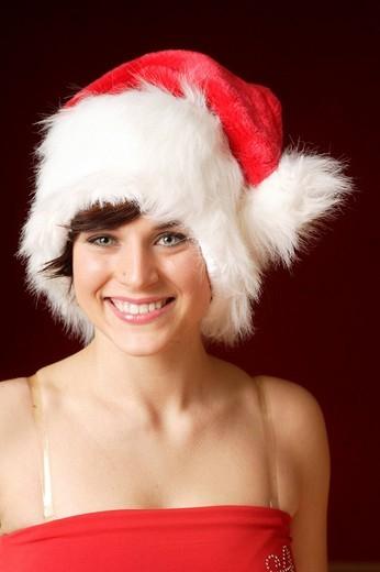 Smiling woman, 23, wearing a Santa Claus hat, portrait : Stock Photo