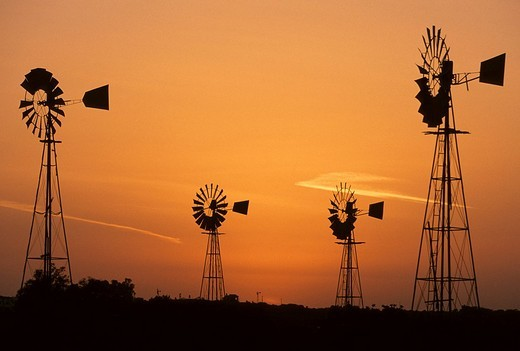 Stock Photo: 1848-86104 Wind driven water pumps silhouetted against evening sunset sky near Protaras, Cyprus