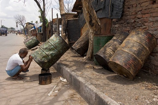Almost everyone in the slums of Topsia earns a living from recycling waste, this man specialises in the reconditioning of old oil barrels, Kolkata, Calcutta, West Bengal, India : Stock Photo