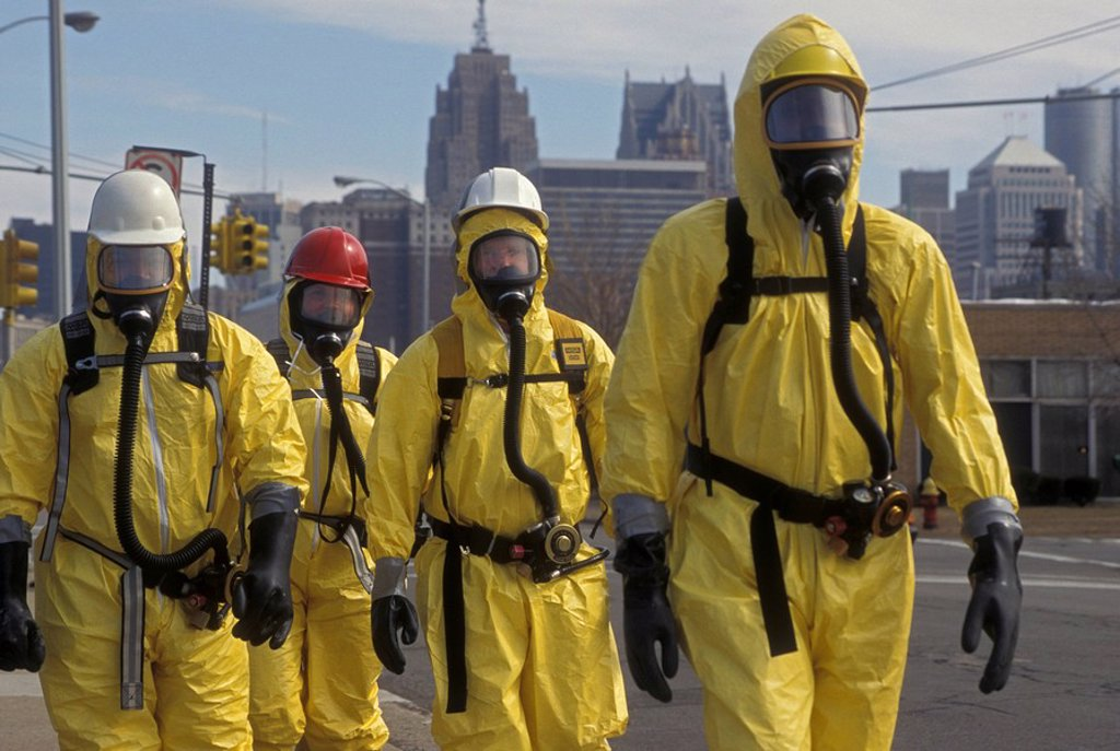 During a training session for workers dealing with toxic chemical spills, participants in protective suits walk down the street, Detroit, Michigan, USA : Stock Photo