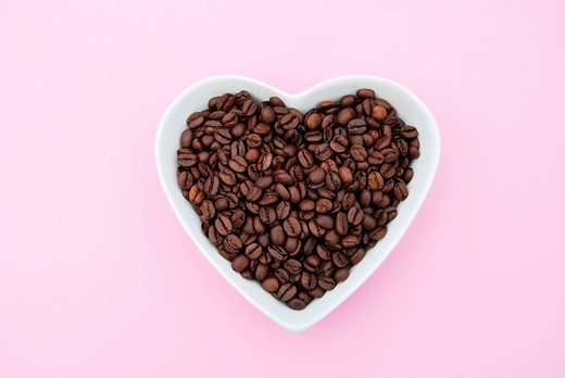 White heart_shaped bowl filled with coffee beans on pink : Stock Photo