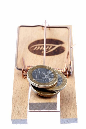 Symbolic shot: coins caught in a mousetrap, debt, credit trap : Stock Photo