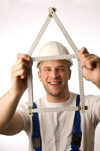 Construction worker holding folding rule yardstick : Stock Photo