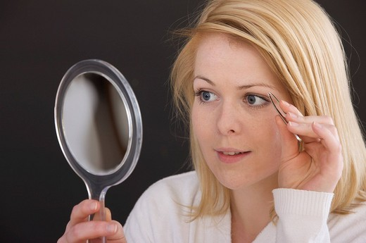 Blonde woman plucking her eyebrows : Stock Photo