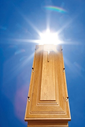 Wooden coffin ascending towards the sky, sun : Stock Photo