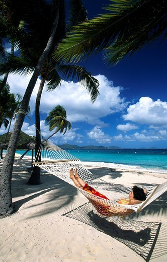 Woman in a hammock under palm trees on a beach on Peter Island, British Virgin Islands, Caribbean : Stock Photo
