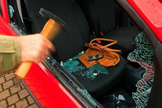 Car burglary, hand with hammer batters the side window, valuables left on the passenger seat, i.e. handbag, purse and mobile phone : Stock Photo