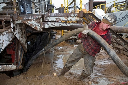 A worker struggles with a hose while dismantling a natural gas drilling rig in the Antrim Shale field of northern Michigan, Mancelona, Michigan, USA : Stock Photo
