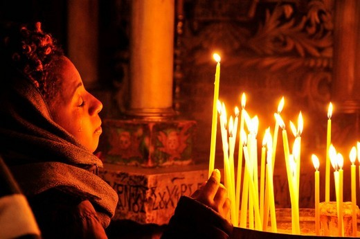 Stock Photo: 1848-9084 Young believer with tears in her eyes lighting a candle at the grave of Christ in the Church of the Holy Sepulchre, Jerusalem, Israel, the Near East, Orient