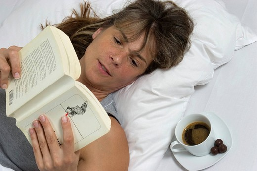Woman lying in bed, book , cup of coffee : Stock Photo