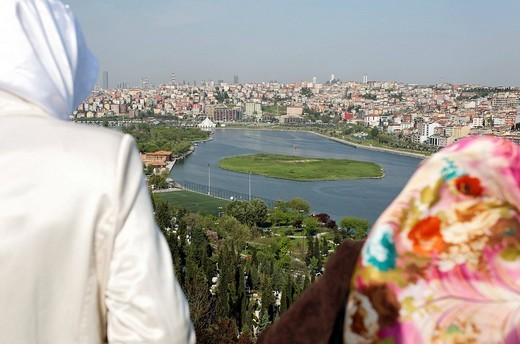 Two Muslim women with headscarves look on the modern suburb Suetluece, Golden Horn, Eyuep, Istanbul, Turkey : Stock Photo